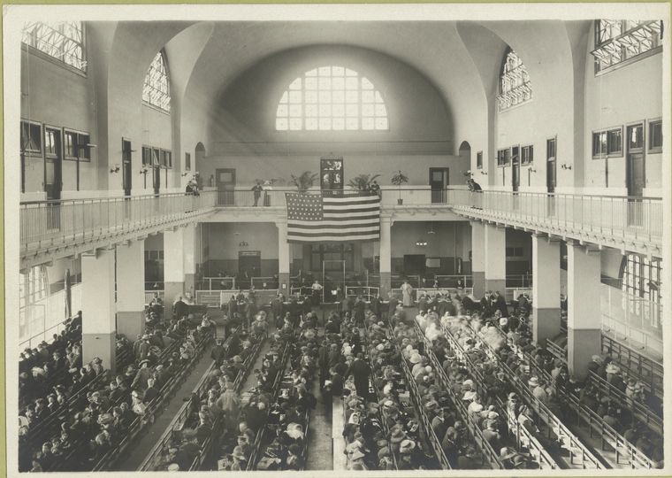 Immigrants seated on long benches in the Main Hall of Ellis Island, c. 1902